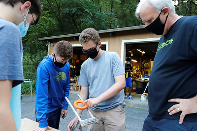 Jacob Noe, (left facing camera) and Nathan Hale work on a robot prototype shooting arm device with team coach Jeff Beckstead advising. (Daniel Corcoran also pictured) Seb Foltz/Butler Eagle 09/24/20