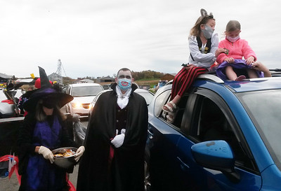 Julianya Smail, left, and her sister Karolyne Smail get some treats from Becky and Mike Werner during the Community Care Connections' Trunk or Treat Halloween event Thursday. The girls were being driven by their mother Kathryn Smail and Debra Halderman. Becky Werner is the director of early intervention progams at Community Care Connections.
