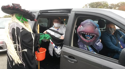 Kathy Perry, adult day service coordinator at Community Care Connections in Connoquenessing Township, hands out candy and treats to Robin Swope, back seat, and Darl Leise during the agency's Trunk or Treat Halloween event Thursday.