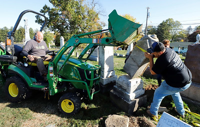 Brian Antoszyk (left) and Cory Fox replace a knocked over tombstone at Saxonburg Cemetary Saturday, part of the Saxonburg Rotary's efforts to fix up the cemetary which includes graves that date back to the 1800s. Seb Foltz/Butler Eagle 10/17/20