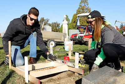 Daniel McFarland and Jamie Antoszyk work to replace fallen tombstones at Saxonburg Cemetary, part of the Saxonburg Rotary's efforts to fix up the cemetary which includes graves that date back to the 1800s. Seb Foltz/Butler Eagle 10/17/20