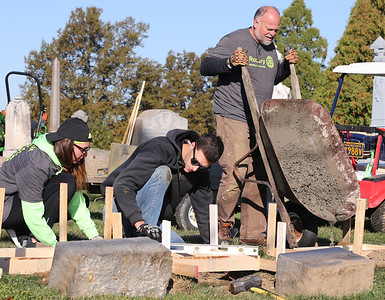 Jamie Antoszyk, Daniel McFarland and Brian Antoszyk work to replace fallen tombstones at Saxonburg Cemetary, part of the Saxonburg Rotary's efforts to fix up the cemetary which includes graves that date back to the 1800s. Seb Foltz/Butler Eagle 10/17/20