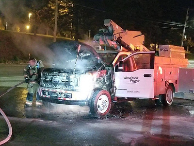 Jim Smith photo. Firefighter Tim Iman of the Butler City Fire Department helps to put out a fire that badly damaged a West Penn Power Company bucket truck about  6:45 a.m. in the parking lot of the former Kervin Subaru dealership on New Castle Road near the state police barracks. The driver was able to get out and he was not injured.