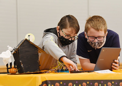 Alex Kamerer,10 and Noah McCall, 10, both of Butler work together on the final touches of a robtics haunted house equiped with servo motors, sensors, and LED lights. Harold Aughton/Butler Eagle