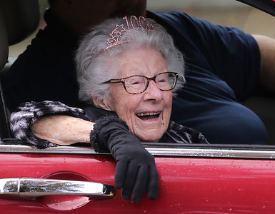 Madeleine Samarco of Cranberry smiles at passers by during her 100th birthday drive-by parade Saturday. Samarco sat in a vehicle while a line of cars filled with family and friends passed waving and delivering gifts to her daughters. Seb Foltz/Butler Eagle. 10/24/20