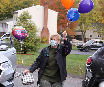 Madeleine Samarco's step daughter Pam Cobak steps out of her car to deliever a birthday gift and baloons during Samarco's 100th birthday parade. Seb Foltz/Butler Eagle 10/24/20