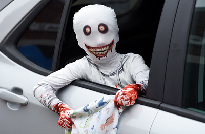 Jack Schmitt, 7, hangs out the window of his family's car as they make their way through the trick or treat drive-through at the Mars Elementary School Monday, October 26. Harold Aughton/Butler Eagle