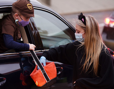 Cole Runyon,6, dressed up as a UPS delivery man to pick up some candy from Mars senionr Maggie Painley during the drive-through trick or treat at the Mars Elementary School. Harold Aughton/Butler Eagle.