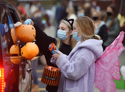 Mars seniors Maggie Painley and Megan Mann handout candy during the drive-through trick or treat event at the Mars Elementary School. Harold Aughton/Butler Eagle.