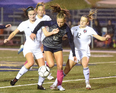 Butler's Samantha Miller (12) fights through challenges from Upper Saint Clair's Elle Snyder (left) and Olivia Amatangelo in Thursday's home playoff win. Miller scored the games opening goal. Butler shut out Upper Saint Clair 4-0. Seb Foltz/Butler 10/29/20