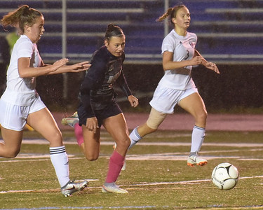 Butler forward Chloe Weiland beats out Upper Saint Clair's Lexi Hall (left) and Bri Lang for a breakaway goal to put the Golden Tornado up 2-0. Weiland scored twice in the 4-0 home playoff win. 10/29/30 Seb Foltz/Butler Eagle