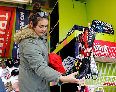 Madison Nicolazzo shows a customer Trump masks at her family's vender stand on Route 228 in Cranberry. Nicolazzo said her family began selling Trump novelties because of Covid-19's  impact on their regular small businesses. Her family owns a number of vape shops and traveling amusement park features. Seb Foltz/Butler Eagle 10/29/20