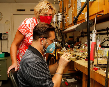 Shelley Mathew of Mathew Jewelers looks over Gregg Eichhorn's shoulder as he works on a ring. Seb Foltz/Butler Eagle