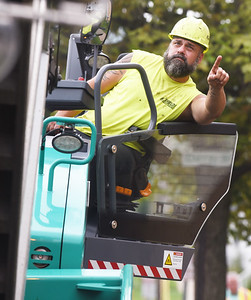 Harold Aughton/Butler Eagle: Ron McDowell of Shields Paving instructors the truck drive to raise the bed of his truck while paving 3rd Street in Butler Wednesday, September 2, 2020.