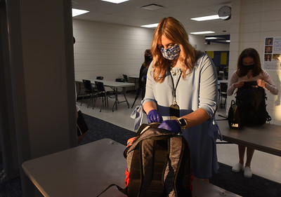 Harold Aughton/Butler Eagle: Courtney Gallagher, a 7th/8th grade ELA and Math teacher at Mars Middle School checks backpacks as students walk through the metal detectors during the first day of school, Tuesday, September 08, 2020.