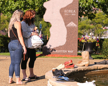 Kailyn Goldinger (left) and Kim Andrews look at the 26 shoes encircling the fountain at Diamond Park Wednesday. Each pair represents one of the 26 suicides in Butler County in 2019. The Butler Suicide Coalition hosted a suicide prevention month presentation Wednesday with guest speakers impacted by suicide. Seb Foltz/Butler Eagle 9/9/20