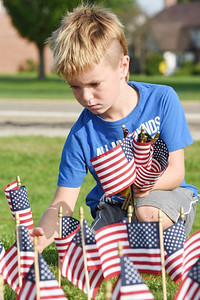 Harold Aughton/Butler Eagle: Fisher Reutzel, 6, of Mars  joined other community members to place 2,977 flags representing those who died in 911 in front of the Mars High School Thursday, September 10, 2020.