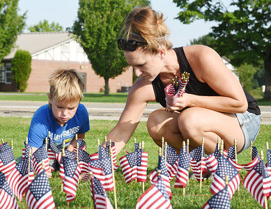 Harold Aughton/Butler Eagle: Fisher Reutzel, 6, of Mars and his mother, Kris Reutzel joined other community members to place 2,977 flags representing those who died in 911 in front of the Mars High School Thursday, September 10, 2020.
