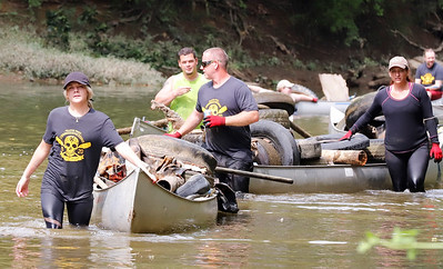 Kate Schorr (left) and Aquatic Alliance president Mike Handley (center) lead a caravan of canoes full of trash to the Harmony Boat Launch during Saturday's Connoquenessing Creek clean-up. Seb Foltz/Butler Eagle 09/12/20