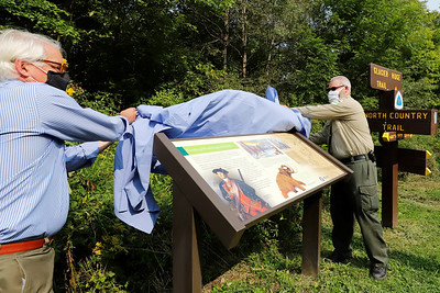 Rodney Gasch (left) of Washington's Trail 1753 and Moraine State Park manager Dustin Drew unveil  a new sign at Morraine's North Country Trail access Wednesday on the Park's North Shore. The sign commemorates George Washington's trip through the region and other historic notes. Seb Foltz/Butler Eagle