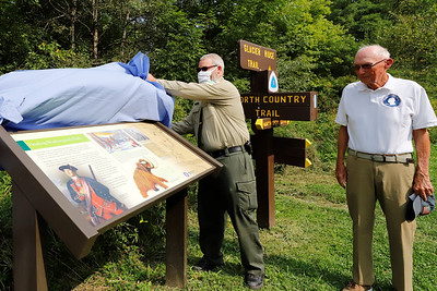 Moraine State Park manager Dustin Drew unveils  a new sign at Morraine's North Country Trail access Wednesday with Washington's Trail 1753 president Martin O'Brien (right) and Rodney Gasch(not pictured) at the Park's North Shore. The sign commemorates George Washington's trip through the region and other historic notes. Seb Foltz/Butler Eagle
