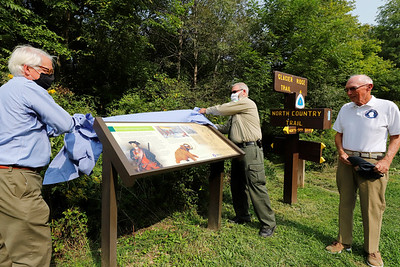 Rodney Gasch (left) of Washington's Trail 1753 and Moraine State Park manager Dustin Drew unveil  a new sign with Washington's Trail president Martin O'Brien at Morraine's North Country Trail access Wednesday on the Park's North Shore. The sign commemorates George Washington's trip through the region and other historic notes. Seb Foltz/Butler Eagle
