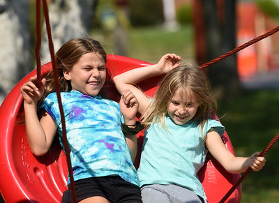 Cousins Eva Tulandin, 9, and Ella Ivin 8, ride the swings at the Zelienople Community Park with Eva's mom Luba Tulandin of Cranberry Tuesday afternoon. Harold Aughton/Butler Eagle