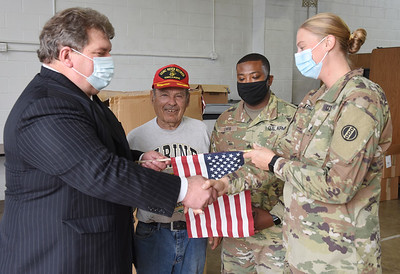 Paul Simms of the Butler Memorial Park Cementary donates the discarded American flags to the Brittni Krill of Veterans Sucide prevention program. Butler Twp. commissioner Sam Zurzola and Nathaniel Lewis look on... Harold Aughton/Butler Eagle