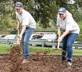 Harold Aughton/Butler Eagle: Members of the Berkshire Hathaway Home Services, Brandon Simmons, left, and Kris Callen, fluff up the mulch at Butler County Children's Center as part of the United Way Day of Caring Mon. Sept. 30.