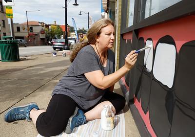 Deborah Frantz with the Butler Art Center works on a mural on the Butler Dental Associates storefront during the this weekends street art festival put on by the Butler Art Center. Seb Foltz/Butler Eagle 09/26/20