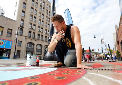 Mike Parker of Lindora works on the sidewalk kraiken during the this weekends street art festival put on by the Butler Art Center. Seb Foltz/Butler Eagle 09/26/20