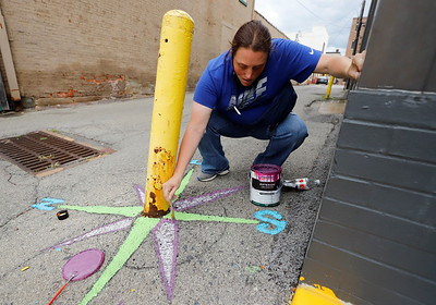 Kayla Roy of Butler paints a compass in an Alley off Main St. near Butler Brew Works during the this weekend's street art festival put on by the Butler Art Center. Seb Foltz/Butler Eagle 09/26/20