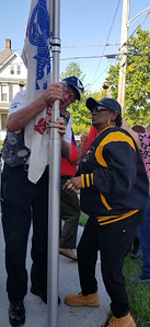 Al Worsley, a board member at Robin's Home in Butler, assists Army veteran Loretta Smith-Jones in raising the Army flag on Saturday. An open house and dedication of the new military flag display was held at Robin's Home, which houses female veterans in need of services or in danger of becoming homeless.