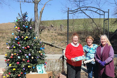 """""""From left, sisters Bonnie, Coralie and Allison Cahill carried on their mother Margaret's Easter egg tree tradition this year. The sisters, who live in the Butler County area, strung up over 2,000 hand-painted eggs on Christmas trees outside Bonnie's home along Saxonburg Road.""""Submitted photo."""