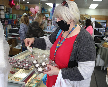 Gloria Lamont of Hooker picks up a box of truffles at Mary's Cakes & Candy Tuesday. Seb Foltz/Butler Eagle 03/30/21