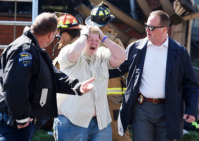 Butler City of Police officers captain Jim Hollobaugh, left, and Lieutenant Chad Rensel attempt to escort resident Andrea Budmark away from the scene of a house fire at 116 Mercer Street Monday afternoon, March 29, 2021.  Harold Aughton/Butler Eagle
