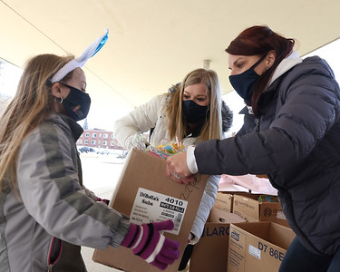 Inspired Hearts and Hands founder Mindy Schnitgen (right) and her daughter Samantha (center) hand her other daughter Lexi a box of food and easter candy to deliver to a car at Saturday's food pickup at Emily Brittain Elementary School. Seb Foltz/Butler Eagle 04/3/21