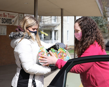 Samantha Schnitgen, 17, of Mars hands kids meals to Emily Brittain Elementary teacher Stephanie Arienzo to deliver to a car at Saturday's food pickup arranged by Inspired Hearts and Hands. Seb Foltz/Butler Eagle 04/03/21