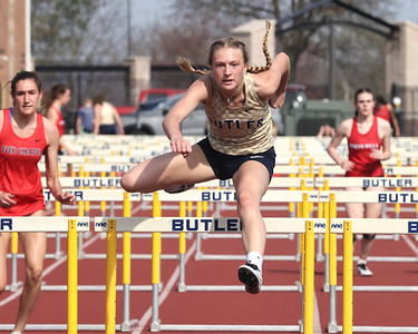 Butler's Emma Lehman clears a hurdle on her way to a win in the 100 meter hurdles during Thursday's home meet against North Hills and Fox Chapel. Seb Foltz/Butler Eagle 04/08/21