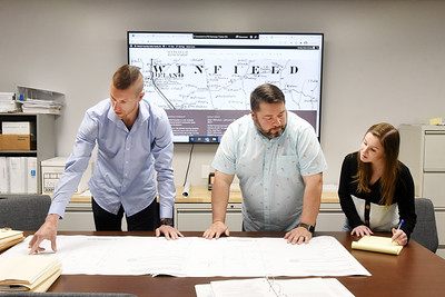 Adam Hartwig, emergency services coordinator, left, and Matt Klabnik, supervisor, study several township maps with township secretary Rachel Altman in the Winfield Township's new emergency operations center Friday, April 9, 2021.