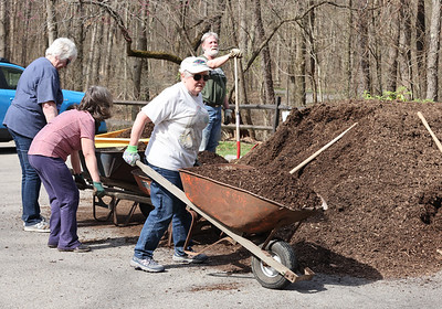 Karen Flanigan (front) and other Moraine McConnells Mill Jennings Commission (3MJC) volunteers load and spread mulch at the entrance to the Jennings Environmental Education Center prairie entrance Saturday. Seb Foltz/Butler Eagle 04/10/21