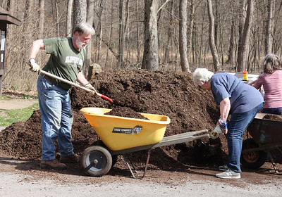 Moraine McConnells Mill Jennings Commission (3MJC) volunteers Chuck Davies and Mary Emmett load mulch to be spread into a flower bed at the Jennings Environmental Education Center prairie entrance Saturday. Seb Foltz/Butler Eagle 04/10/21