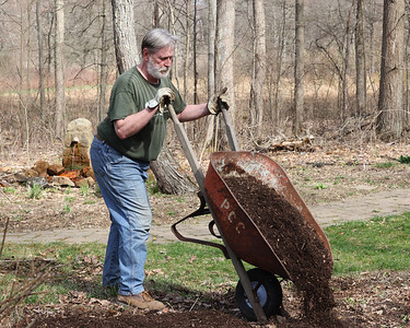 Moraine McConnells Mill Jennings Commission (3MJC) volunteer Chuck Davies dumps mulch into a flower bed at the entrance to the Jennings Environmental Education Center prairie entrance Saturday. Seb Foltz/Butler Eagle 04/10/21