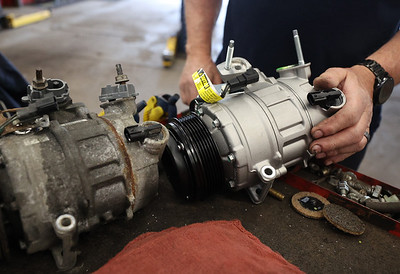 Mark King shows the difference between a new and old air conditioning air compressor. A broken compressor can be enough to snap the belt that also runs the engine's alternator, causing car failure. Seb Foltz/Butler Eagle.  April 2021