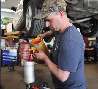 Chad Straessley of Milbert's Car Care pours transmision fluid into a machine to flush the transmission on a vehicle. Seb Foltz/Butler Eagle April 2021