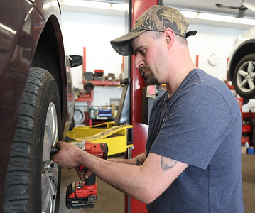 Chad Straessley of Milbert's Car Care rotates tires on a vehicle in the Cranberry-area shop. Seb Foltz/Butler Eagle April 2021