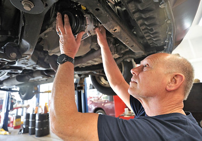 Mark King of Milbert's Car Care in Cranberry replaces the compressor on a car's airconditioning system. When a compressor's ball barings fail, it can cause the belt that also charges the alternator to snap, leading to engine failure. Seb Foltz/Butler Eagle 04/07/21