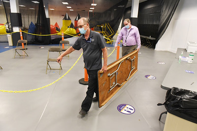 Butler Health System environmental services employees Kirk Eury, left, and Don Woodward, manager, setup tables and chairs at the former Sears building at the Clearview Mall Tuesday afternoon. April 13, 2021.  Harold Aughton/Butler Eagle.