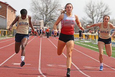 Slippery Rock's Anna Kadlubek crosses the finish line to earn first place in the 100 meter dash, edging out Butler's Justine Forbes (left) and Taylor Timmons in Saturday's Butler County Classic. Forbes and Timmons finished second and third. Schools from across the county participated in the one day event. Seb Foltz/Butler Eagle 04/10/21