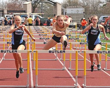 Butler's Emma Lehman clears the final hurdle on her way to a win in the 100 meter hurdles against Seneca's Kiersten Belt and Julie Snyder in Saturday's Butler Classic track meet. Belt and Snyder finished second and third respectively. Schools from across Butler County came to compete in the one day event. Seb Foltz/Butler Eagle 04/10/21